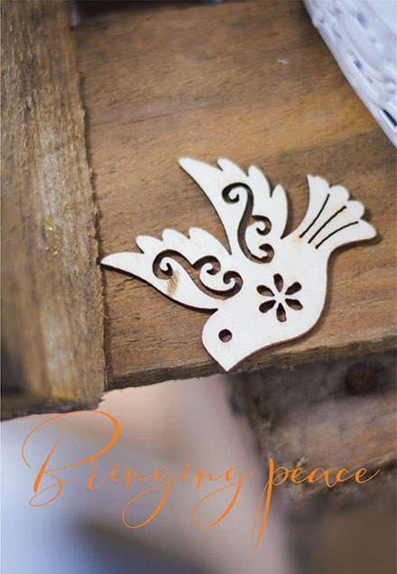 Wood cutout of dove with caption 'Bringing peace'